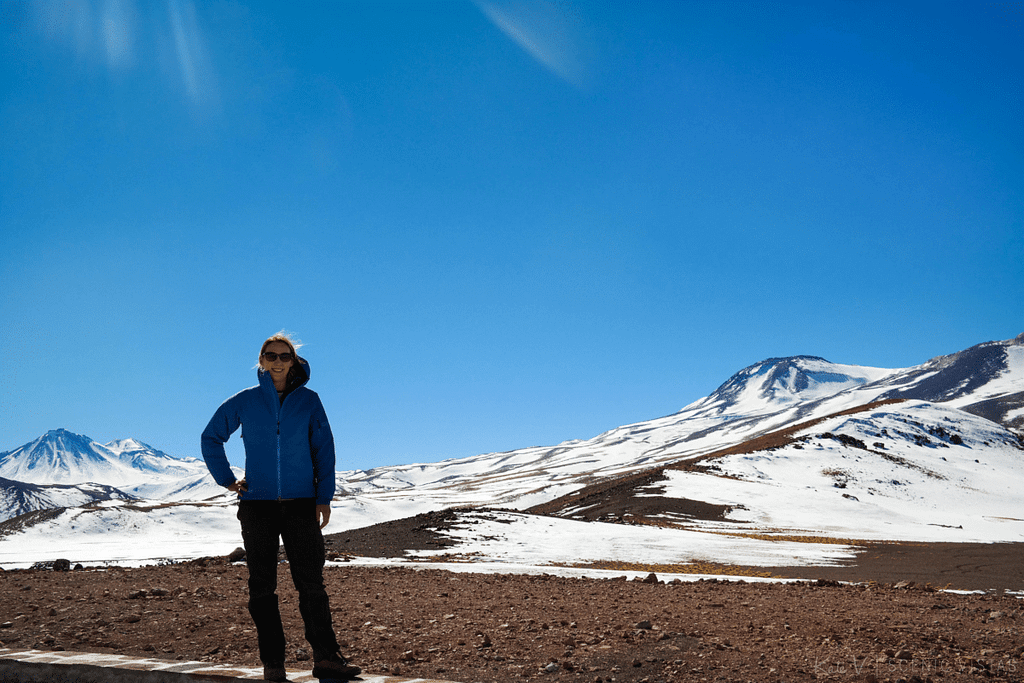 Woman standing in front of snow-capped mountains of the Lagunas Altiplanicas in Chile.
