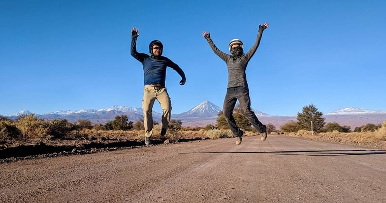 Jumping tourist photo of a couple on a dirt road in the Atacama Desert.