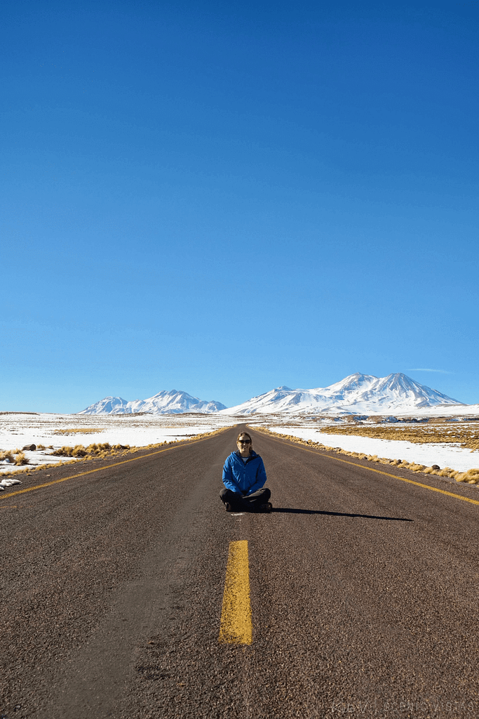 Woman sits in the road in front of snow-capped mountains of the Lagunas Altiplanicas.