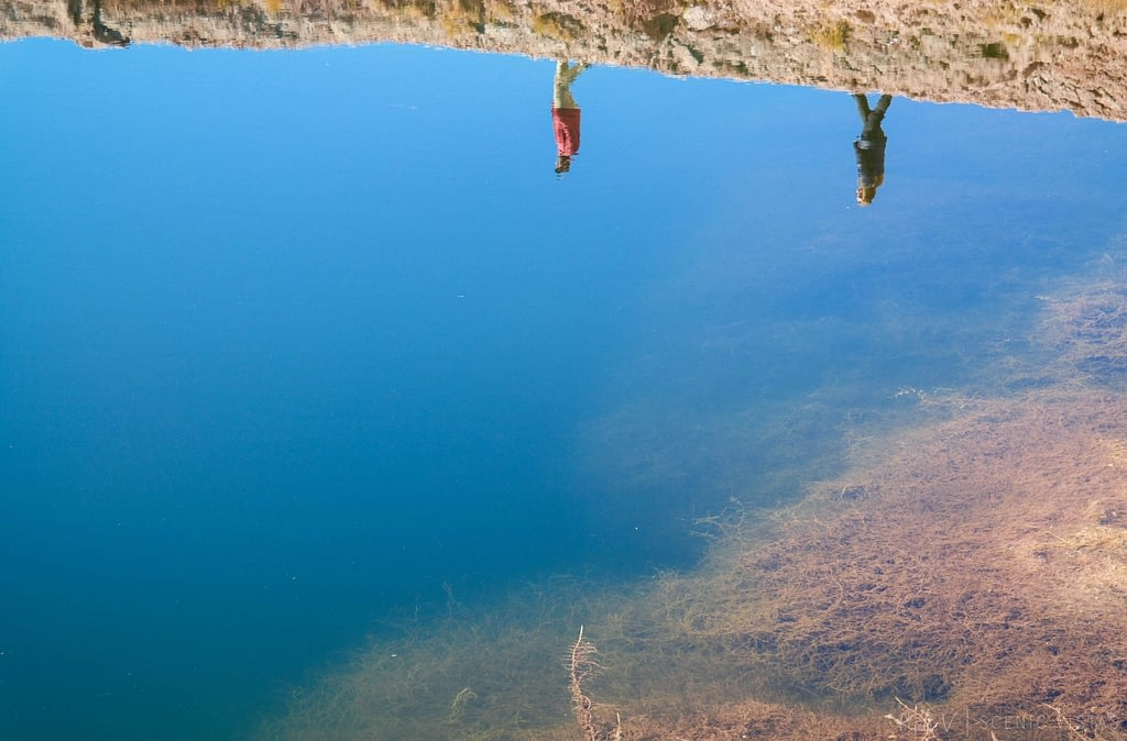 Reflection of a couple walking in the water of the Ojos del Salar in the Atacama.