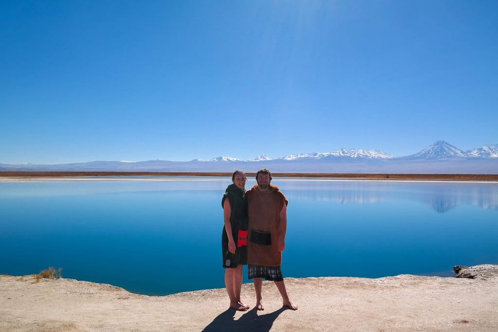 Couple wearing robes standing near Laguna Cejar after getting out of the water.