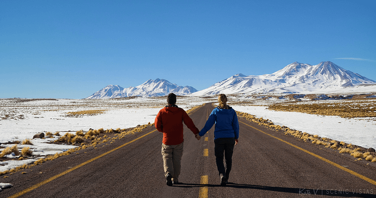 Couple holding hands while strolling down a road in the Lagunas Altiplanicas region of the Chilean desert.
