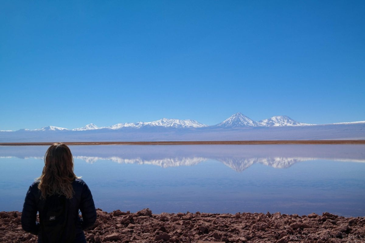 Woman standing near Laguna Tebenquiche taking in the mountain reflection.