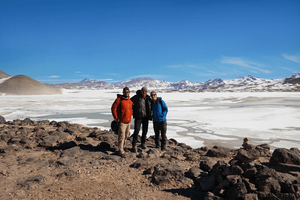 Friends standing in front of frozen Piedras Rojas in the Lagunas Altiplanicas.