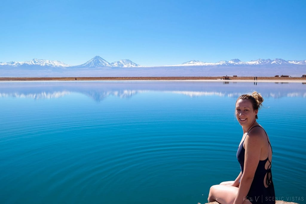 Woman sitting on the edge of Laguna Cejar, about to jump in the water.