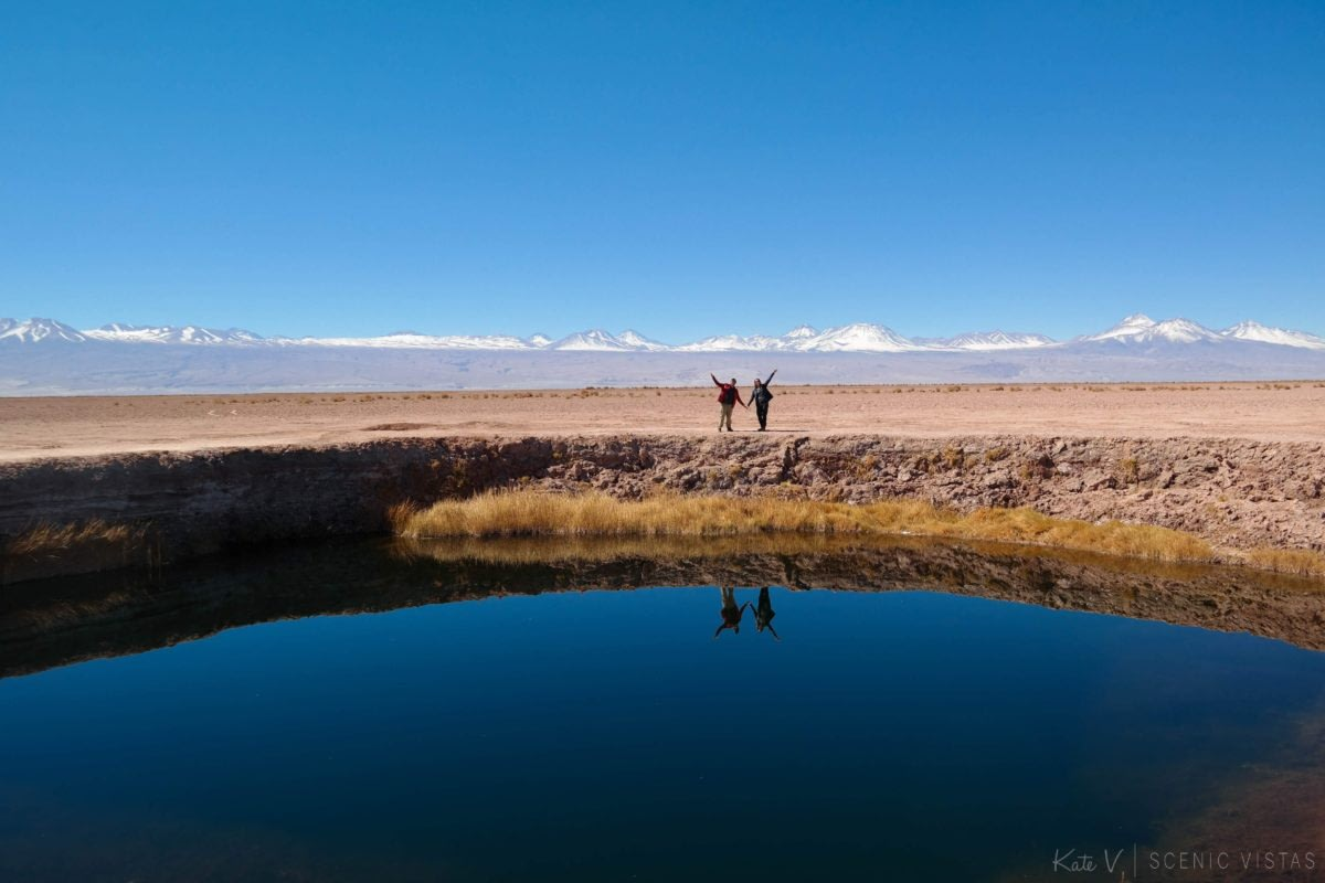 Couple posing behind the Ojos del Salar with their reflection showing in the water.