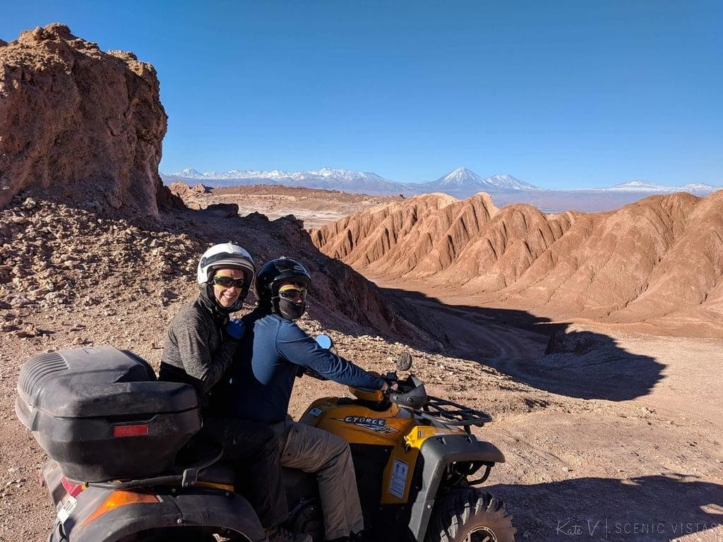 Couple riding an ATV in front of the lunar landscape of the Cordillera de la Sal.