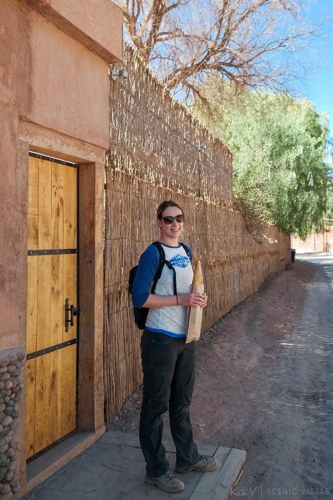 Woman holding a baguette on the streets of San Pedro de Atacama.