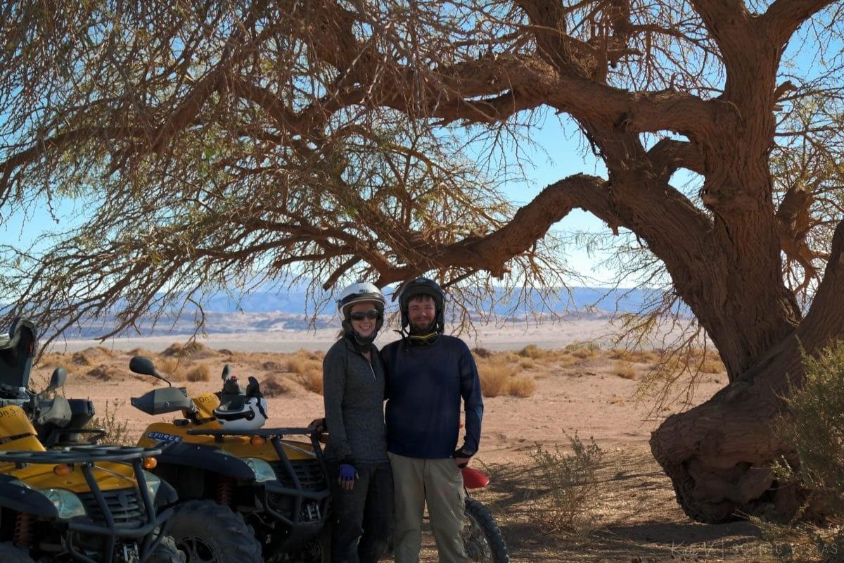 Couple posing next to an ATV under a tree in the Atacama Desert.